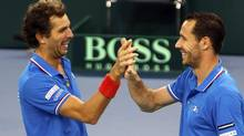 French team Michael Llodra and Julien Benneteau (L) celebrate after defeating Jonathan Erlich and Dudi Sela of Israel in their first round Davis Cup tennis match in Rouen, February 2, 2013. France qualified for the next round. (CHARLES PLATIAU/REUTERS)