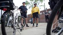 Police Sergeant James Hogan and Constable Tony Correa survey the scene of an accident they came across during their regular bike patrol of 12 Division. (Anne-Marie Jackson)