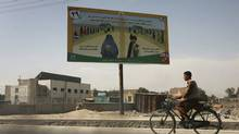 An Afghan youth rides his bike, passing by an election billboard that asks the people to vote, in Kabul, Afghanistan on Monday, Oct. 19, 2009. (Musadeq Sadeq)