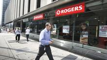 A man walks by a Rogers store at Yonge and Eglinton, Toronto, August 27, 2013. (Gloria Nieto/The Globe and Mail)
