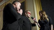 Sir Elton John, centre, and husband David Furnish are interviewed by a TV presenter as they arrive at the opening night of 'Billy Elliot the Musical' in Toronto on March 1, 2011. (Chris Young/Chris Young/The Canadian Press)