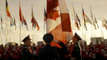 Russian soldiers raise the Canadian flag during a welcome ceremony for the Canadian Olympic team ahead of the 2014 Winter Olympics, Wednesday, Feb. 5, 2014, in Sochi, Russia. (Vadim Ghirda/AP)