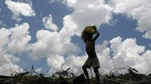 A ragpicker carries a sack on his head in the northeastern Indian city of Siliguri July 3, 2007.