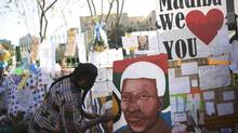A man paints a portrait of ailing former South African President Nelson Mandela outside the Medi-Clinic Heart Hospital where he is being treated in Pretoria June 26, 2013. (DYLAN MARTINEZ/REUTERS)