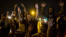Protesters gather after a state imposed midnight curfew in Ferguson, Mo, August 17, 2014. Hours after Gov. Jay Nixon of Missouri imposed a midnight-to-5 a.m. curfew on Saturday, a group of protesters defied the order and violence flared briefly on Sunday morning, a week after demonstrations erupted over the killing of an unarmed black teenager by a white police officer. (ERIC THAYER/NYT)
