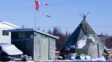 The remains of a Canadian flag can be seen flying over a building in Attawapiskat, Ont., on Nov. 29, 2011. (Adrian Wyld/The Canadian Press/Adrian Wyld/The Canadian Press)