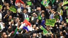 Brazil's lawmakers celebrate after they reached the votes needed impeach President Dilma on April 17. The political turmoil in Brazil has made Alex Cuadros' Brazillionaires more relevant than ever. (EVARISTO SA/AFP/Getty Images)
