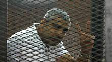 Canadian-Egyptian journalist Mohamed Fahmy gestures from the defendant's cage during a sentencing hearing in a courtroom in Cairo on June 23, 2014. (AHMED ABD EL LATIF/ASSOCIATED PRESS)