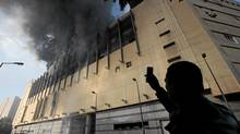 An Egyptian man uses his mobile phone to take a picture of the Arcadia shopping center, that was looted, damaged and set on fire by people in Cairo, Egypt, Sunday Jan. 30, 2011. (Lefteris Pitarakis/Lefteris Pitarakis/The Associated Press)