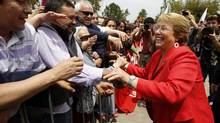 Chilean presidential candidate Michelle Bachelet greets supporters during a campaign event in Santiago Nov. 18, 2013. Bachelet was the clear winner in Chile's presidential election on Sunday, although she will have to wait until a second round runoff next month to seal her victory. (IVAN ALVARADO/REUTERS)
