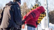 A young man from Yemen is handcuffed by an RCMP officer after crossing the U.S.-Canada border into Canada near Hemmingford, Que., on Friday, February 17, 2017. For many asylum-seekers crossing from the United States into Canada, Roxham Road in the small Quebec town of Hemmingford represents the first steps of a potential new life. THE CANADIAN PRESS/Paul Chiasson
