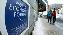 People walk past the logo of the World Economic Forum in front of the congress center in the Swiss mountain resort of Davos on Jan. 22, 2012. (ARND WIEGMANN/ARND WIEGMANN/REUTERS)