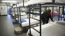 A worker prepares beds at the Gateway Shelter in Surrey, B.C., on Nov. 6, 2015. (Rafal Gerszak For The Globe and Mail)