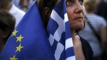 A pro-Euro protester holds a European Union and a Greek national flag during a rally in front of the parliament building in Athens, Greece, July 9, 2015. REUTERS/Alkis Konstantinidis (© Alkis Konstantinidis / Reuter/REUTERS)