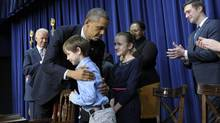 President Barack Obama, accompanied by Vice-President Joe Biden, hugs eight-year-old letter writer Grant Fritz during a news conference on proposals to reduce gun violence. (Susan Walsh/AP)