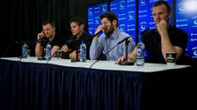 From left, Vancouver Canucks' Henrik Sedin, Kevin Bieksa, Ryan Kesler and Daniel Sedin attend an end of season news conference in Vancouver, April 14, 2014. (DARRYL DYCK/THE CANADIAN PRESS)