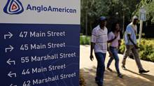 People walk past a board outside the Anglo American offices in Johannesburg January 8, 2013. (SIPHIWE SIBEKO/Reuters)