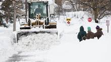 Heavy machinery clears snow from a street following an autumn storm in Buffalo, New York, November 20, 2014. (AARON LYNETT/REUTERS)