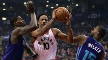 Toronto Raptors guard DeMar DeRozan tries to get through Charlotte Hornets guard Kemba Walker and Charlotte Hornets forward Marvin Williams during first half NBA basketball action, in Toronto on Wednesday, March 29, 2017. (Frank Gunn/THE CANADIAN PRESS)