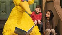 In this April 10, 2008 file photo, Big Bird reads to Connor Scott and Tiffany Jiao during a taping of Sesame Street in New York. (MARK LENNIHAN/AP)
