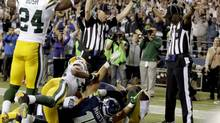 Officials signal a touchdown by Seattle Seahawks wide receiver Golden Tate, obscured, on the last play of an NFL football game against the Green Bay Packers, Monday, Sept. 24, 2012, in Seattle. The Seahawks won 14-12. (Stephen Brashear/AP)
