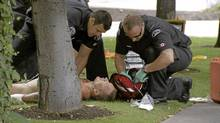 Paramedics assist a man who was injured in a gang - related shooting outside a casino in Kelowna, B.C. on Sunday, Aug. 14, 2011. (CTV photo/CTV photo)