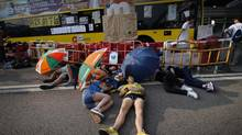 Student activists sleep in the shade of umbrellas, on a road near the government headquarters where pro-democracy activists have gathered and made camp, Tuesday, Sept. 30, 2014, in Hong Kong. (Wong Maye-E/AP)