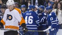 Toronto Maple Leafs' Nick Spaling (16) celebrates with teammates after scoring as Philadelphia Flyers' Evgeny Medvedev (82) skates past during second period NHL hockey action, in Toronto on Saturday, Feb. 20, 2016. (Chris Young/THE CANADIAN PRESS)
