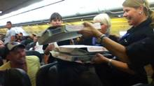 A Frontier Airlines flight attendant passes out pizza to passengers aboard a Denver-bound flight diverted to Cheyenne, Wyo., on July 7, 2014. (LOGAN MARIE TORRES/ASSOCIATED PRESS)