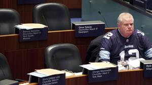 Toronto Mayor Rob Ford, wearing an Argos CFL jersey, sits in council chambers as he awaits a motion to strip him from Mayoral powers following a tumultuous day at City Hall.