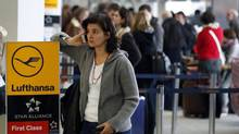 A woman makes a telephone call as passengers queue in front of Lufthansa counters at the airport Berlin Tegel, Germany, Thursday, March 21, 2013. German carrier Lufthansa cancelled around 700 flights due to a massive strike across the country's main air traffic hubs. (Michael Sohn/AP)