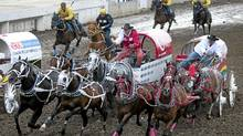Driver Rae Croteau Jr., right, in white, guides his team around the second barrel during chuckwagon racing action at the Calgary Stampede in Calgary, Monday, July 12, 2010. (Jeff McIntosh/The Canadian Press/Jeff McIntosh/The Canadian Press)