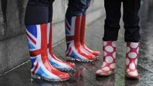 People wait in the rain wearing wellington boots for the start of the Thames pageant near Tower Bridge in London June 3, 2012. (PHILIP BROWN/REUTERS)