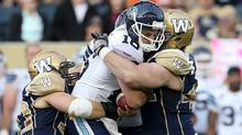 Toronto Argonauts' quarterback Mitchell Gale (16) is sacked by Winnipeg Blue Bombers' Greg Peach (90) and Zach Anderson (44) during the first half of preseason CFL football action at Investors Group Field in Winnipeg, Monday, June 19, 2013 (The Canadian Press)