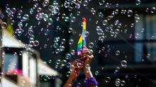 A woman holds a rainbow flag as bubbles float in the air during the Vancouver Pride Parade in Vancouver, B.C., on Sunday August 4, 2013. (Darryl Dyck/The Canadian Press)