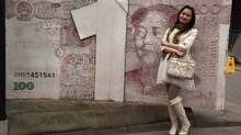 A Chinese woman poses for photos near a sculpture depicting the Chinese yuan note at an art district in Beijing. (Ng Han Guan/Ng Han Guan/Associated Press)