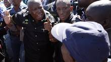 Firebrand politician Julius Malema, left, argues with police officers at Lonmin Platinum Mine near Rustenburg, South Africa. Mr. Malema, who was axed from the ruling ANC party, has used the unrest to fire up worker frustrations and lobby for wildcat stoppages. (Themba Hadebe/AP)