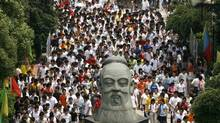 FILE PHOTO: Students walk past a statue of the ancient Chinese educationalist Confucius, as they finish an exam of the National College Entrance Exams in Wuhan, central China's Hubei province, June 7, 2007. (Stringer/Reuters)