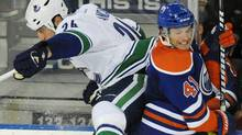 Vancouver Canucks' Mark Mancari, left, checks the Edmonton Oilers' Taylor Chorney during second period NHL preseason hockey action in Edmonton on Thursday, September 22. (John Ulan/The Canadian Press)