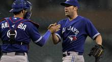 Toronto Blue Jays closer pitcher Casey Janssen (R) and catcher J.P. Arencibia celebrate in the rain their victory against the Detroit Tigers during the ninth inning of their American League baseball game in Detroit, Michigan April 10, 2013. (REBECCA COOK/REUTERS)