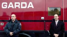 Garda CEO Stéphan Crétier (right) stands with a security officer next to a company truck in this file photo. (Ivanoh Demers/CP)