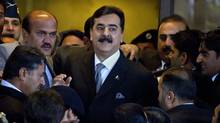 Pakistani Prime Minister Yousuf Raza Gilani is surrounded by security personnel as he arrives at the Supreme Court for a hearing, in Islamabad on Feb. 13, 2012. (Anjum Naveed/AP/Anjum Naveed/AP)
