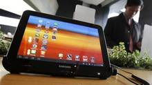 A visitor looks around behind Samsung Electronics' Galaxy Tab 10.1 tablet displayed for customers at a registration desk at South Korean mobile carrier KT's headquarters in Seoul December 9, 2011. (STRINGER/KOREA/REUTERS)