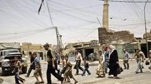 In this June 8, 2009 file photo, residents walk past the crooked minaret in a busy market area in Mosul, Iraq. Iraq's ministry of defense says Islamic State militants destroyed the al-Nuri mosque in Mosul and the adjacent iconic leaning minaret when fighters detonated explosives inside the structures. (Maya Alleruzzo/AP)