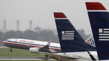 An American Airlines jet takes off while U.S. Airways jets are lined up at Reagan National Airport in Washington in this file photo taken on July 12, 2013. (LARRY DOWNING/REUTERS)