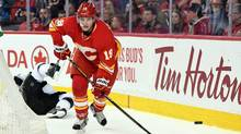 Calgary Flames left wing Matthew Tkachuk chases after the puck after a collision with Los Angeles Kings defenseman Drew Doughty during the first period at the Scotiabank Saddledome in Calgary, on March 19, 2017. (Candice Ward/USA Today Sports)