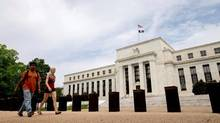 In this June 19, 2015, file photo, people walk past the Marriner S. Eccles Federal Reserve Board Building in Washington.