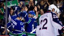Vancouver Canucks' Mason Raymond, from left, Daniel Sedin, of Sweden, and Henrik Sedin, of Sweden, celebrate Daniel Sedin's goal as Columbus Blue Jackets' Vinny Prospal, right, of the Czech Republic, skates to the bench during the first period of an NHL hockey game in Vancouver, B.C., on Saturday March 17, 2012. (DARRYL DYCK/THE CANADIAN PRESS)