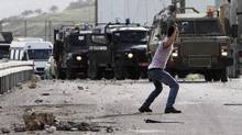 A Palestinian protester uses a sling to throw a stone at Israeli military jeeps during clashes at Hawara checkpoint near the West Bank city of Nablus, Feb. 25, 2013. (ABED OMAR QUSINI/REUTERS)