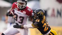 Calgary Stampeders' Romby Bryant tries to fend off a tackle by Hamilton Tiger Cats' Malt Bucknor during CFL action at Ivor Wynne Stadium in Hamilton, Ontario, Thursday, Aug. 9, 2012. (Geoff Robins/THE CANADIAN PRESS)
